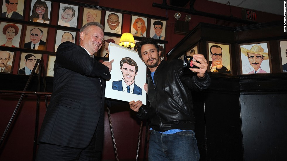 Actor James Franco, right, snaps a photo of himself and a caricature of himself at Sardi's restaurant in New York on Wednesday, May 21. At left is restaurant owner Max Klimavicius.