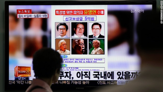 A TV news program shows a wanted poster of Yoo Byung Eun with a $500,000 reward for  tips about his whereabouts.