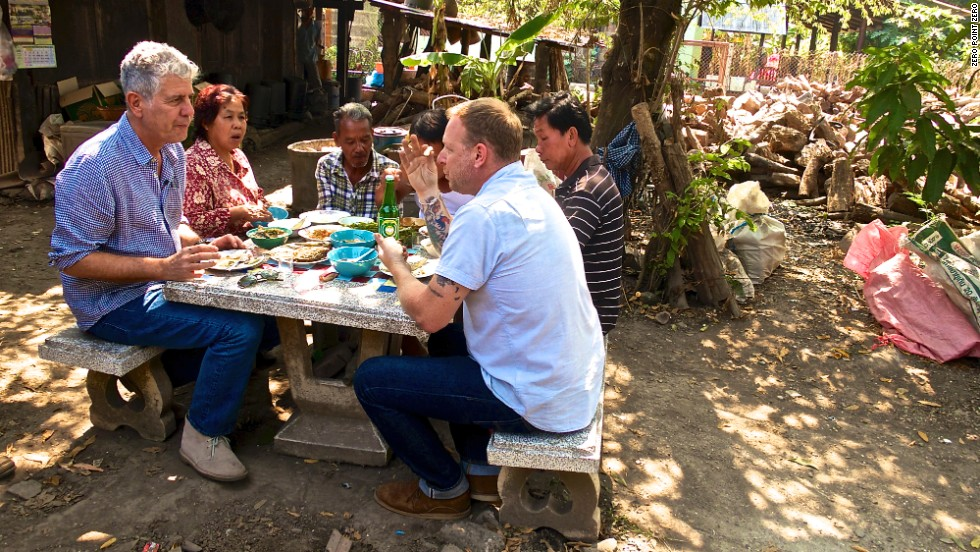 Bourdain and Ricker eat various fried fish, Tom Som Gai, Namphrik Om and other northern specialties during a lunch break at the distillery.