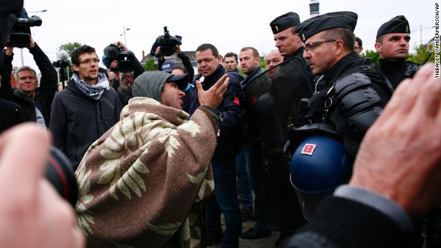 An Afghan migrant argues with French police officers after French authorities started to dismantle makeshift camps in Calais.