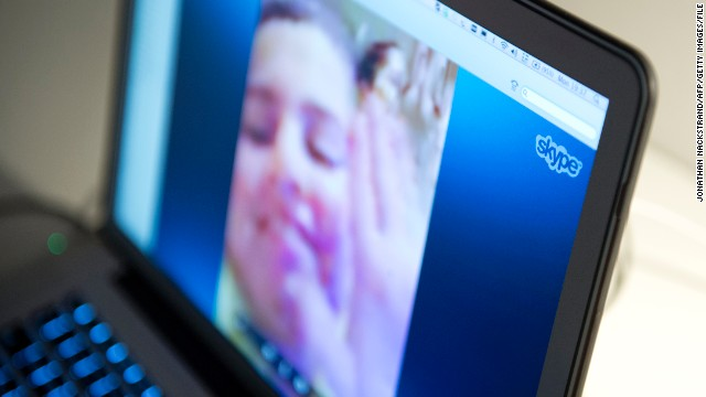 A woman in Sweden communicates with her family abroad by using Skype.