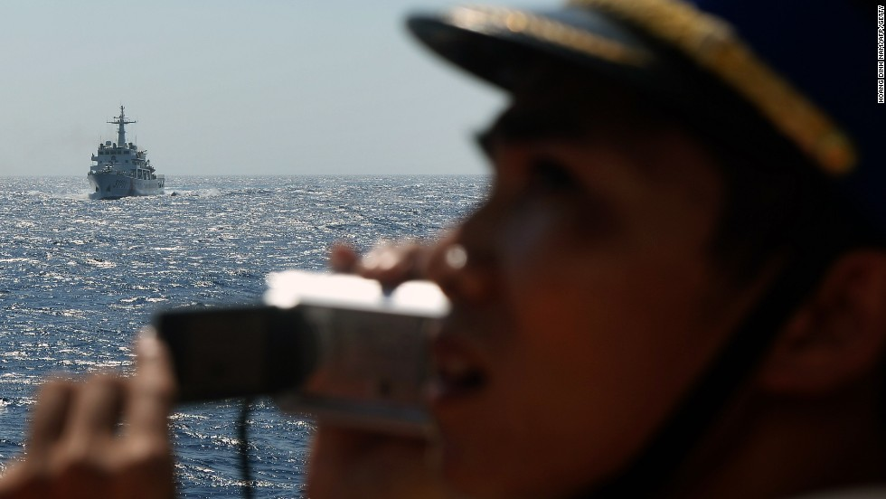 This picture taken from a Vietnam Coast Guard ship shows a Vietnamese Coast Guard officer taking picture of an approaching China Coast Guard ship.