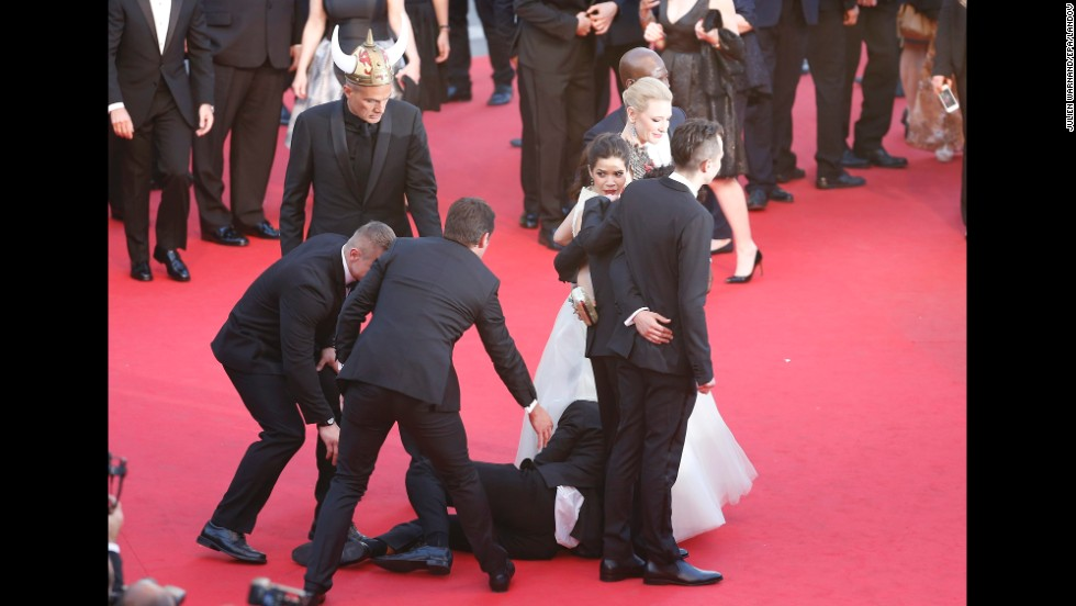 Security guards quickly pull Sediuk away from under the dress of actress America Ferrera on the red carpet at the 2014 Cannes Film Festival in France on May 16.