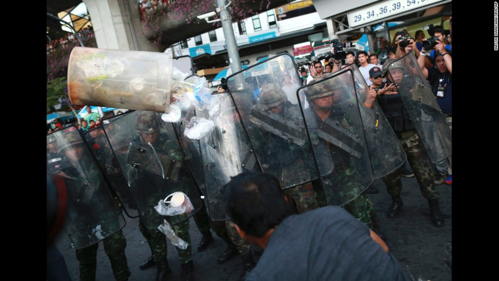 A protester throws a garbage can at a line of Thai soldiers during an anti-coup demonstration in Bangkok on May 28.