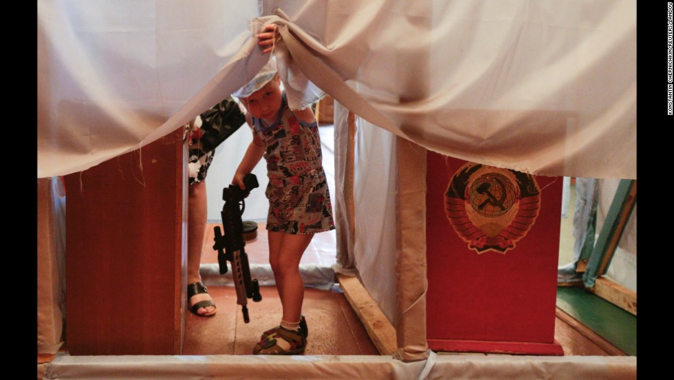 "A child holds a toy gun as voters fill out their ballots in the village of Kodra, Ukraine, on Sunday, May 25. A new president, Petro Poroshenko, was <a href=""http://www.cnn.com/2014/05/27/world/gallery/ukraine-after-election/index.html"">elected in Ukraine</a>, three months after the ouster of Viktor Yanukovych. But there is still unrest in the eastern part of the country, where there is a large separatist movement following Russia's takeover of the Crimean peninsula."