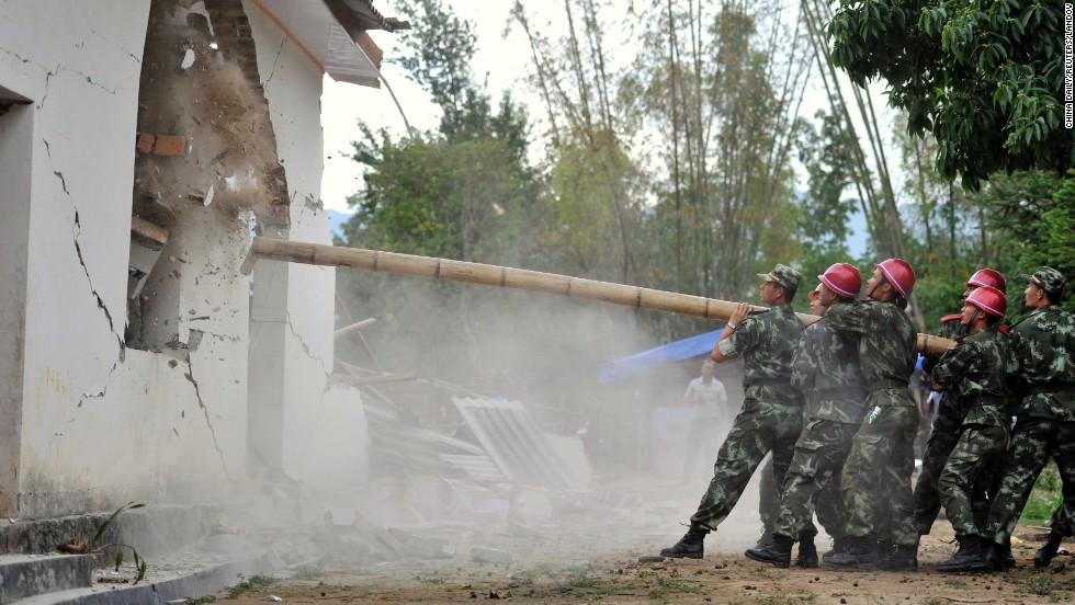 Paramilitary policemen demolish an unstable building after a 5.6-magnitude earthquake hit China's Yingjiang County on Saturday, May 24.