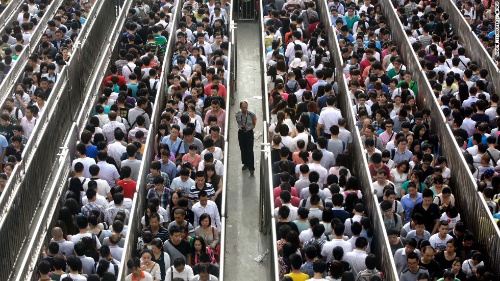 A security guard watches passengers line up at a subway station checkpoint during morning rush hour in Beijing on Tuesday, May 27.