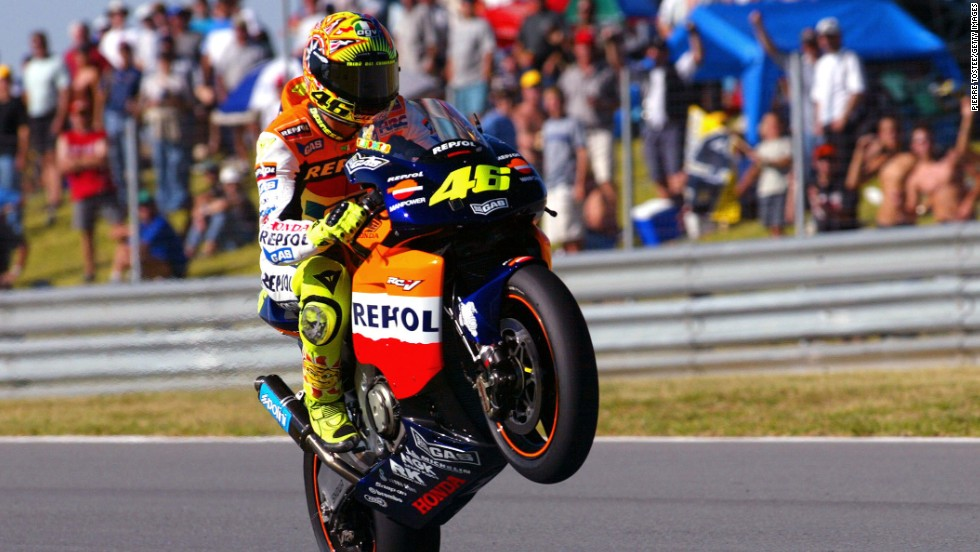 Rossi performs a wheelie after taking pole position on his Honda at the MotoGP in South Africa in 2002.