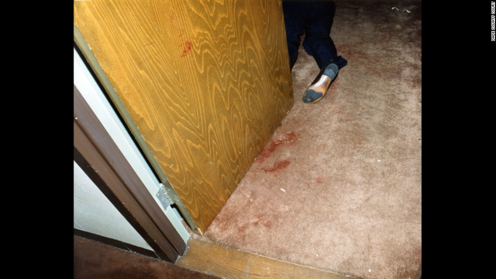 On October 16, 1986 police found the Moo Youngs' bloody bodies in Room 1215 at Miami's Dupont Plaza Hotel. This police evidence photo shows one of the bodies in a doorway.