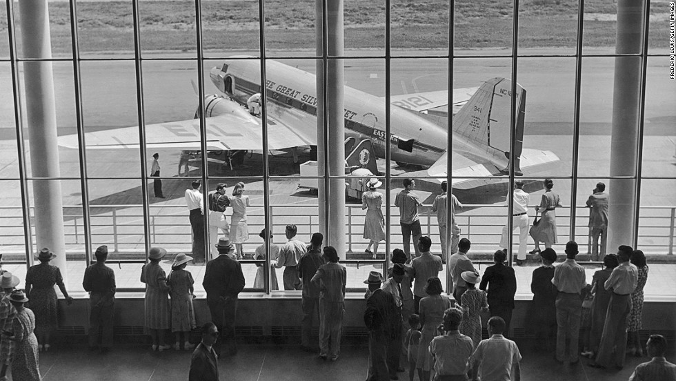 "An Eastern Air Lines DC-3, which was known as ""The Great Silver Fleet"" during its heyday, is seen through an airport viewing gallery in 1945."