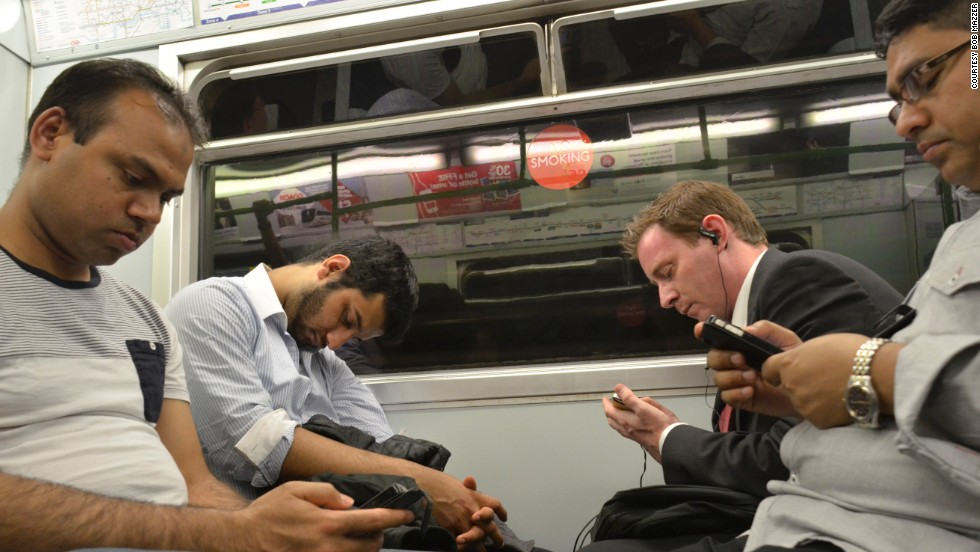 Mazzer says photographing the underground has shown how people have changed from reading newspapers and smoking, to becoming attached to their iPads and smartphones, like these men from 2013.