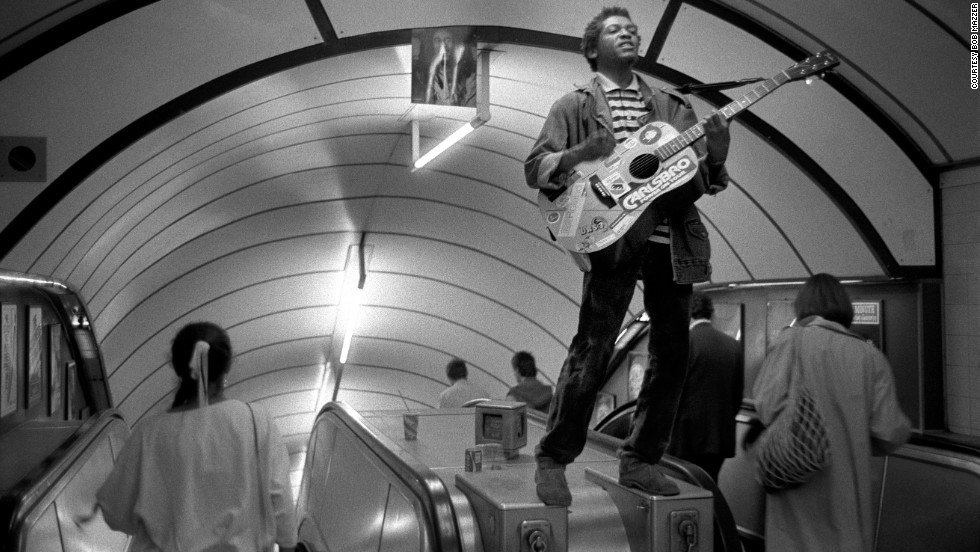 This musician had clambered on an escalator to play his guitar in the early 80s, after Bob Marley had died. The musician had pinned a  picture of Marley to the ceiling.