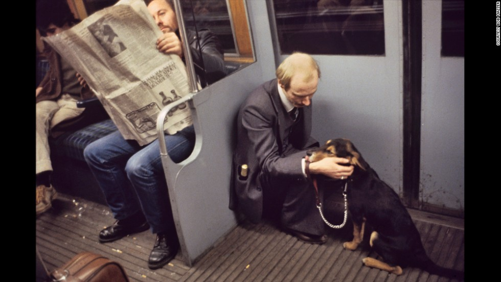 "Here, a man takes comfort from his dog. ""I remember being so touched by the whole scene,"" Mazzer says, noting the rarity of a adult sitting on the floor. It seemed ""so sweet...a man's best friend in his hour of need."""