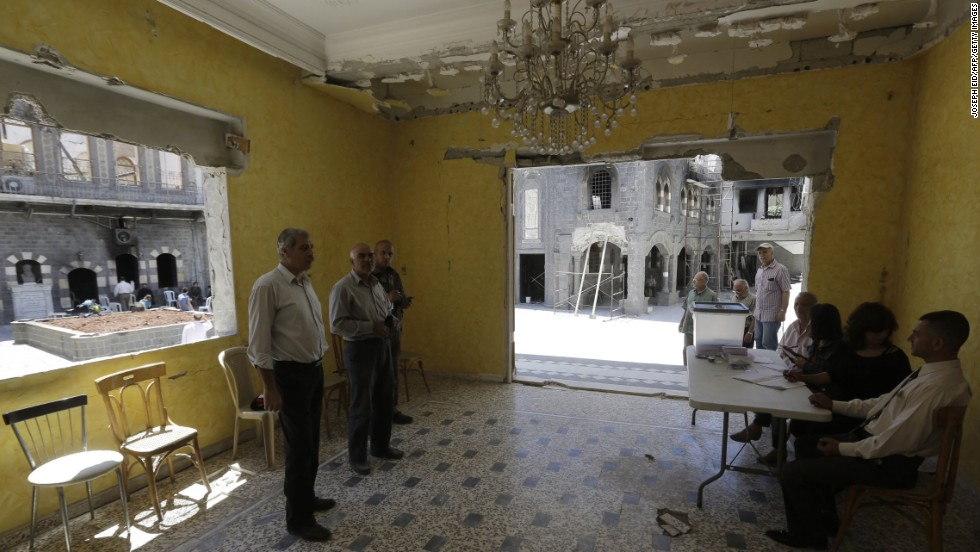 Syrians cast their votes in the damaged courtyard of the Umm al-Zunnar church in Homs on June 3.