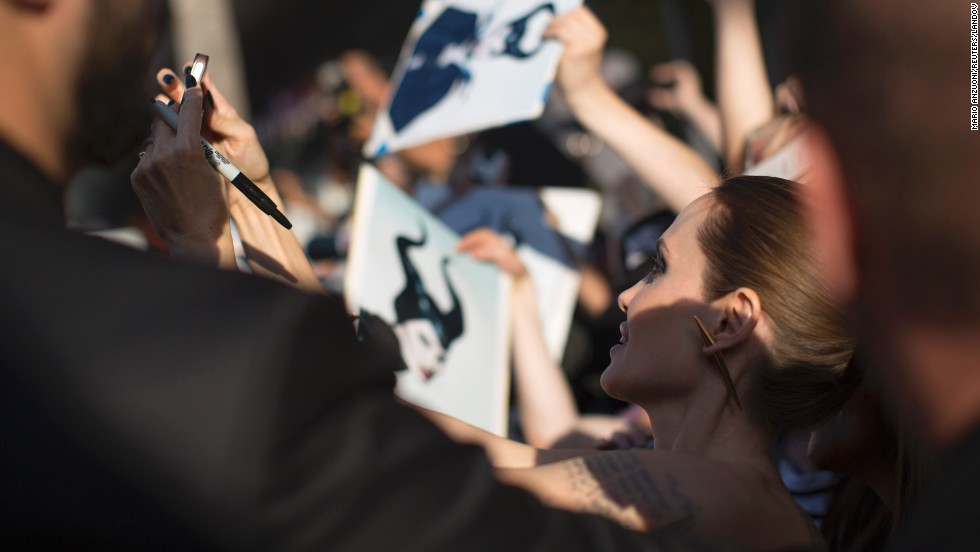 "Actress Angelina Jolie poses for a selfie with a fan Wednesday, May 28, at the Hollywood premiere of her movie ""Maleficent."""