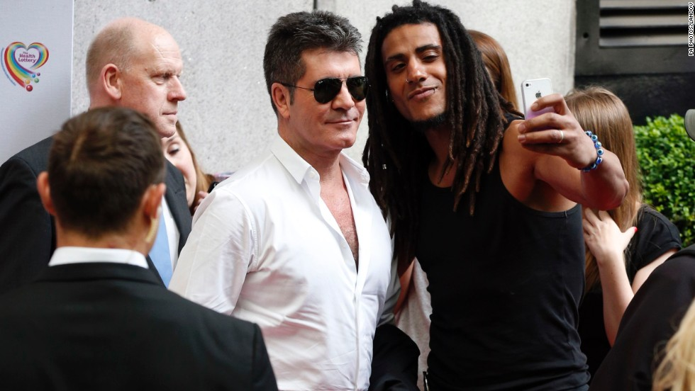 Television personality Simon Cowell, left, poses for a selfie Monday, June 2, as he arrives at the Savoy Hotel in London for the Health Lottery Tea Party charity fundraiser.