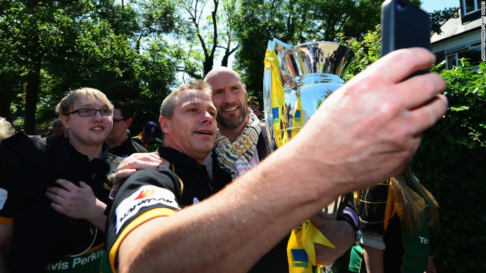 Retired rugby star Lawrence Dallaglio poses with fans as he carries the Aviva Premiership Trophy to London's Twickenham Stadium before the Premiership final between Saracens and Northampton Saints on Saturday, May 31. Northampton won the final 24-20.