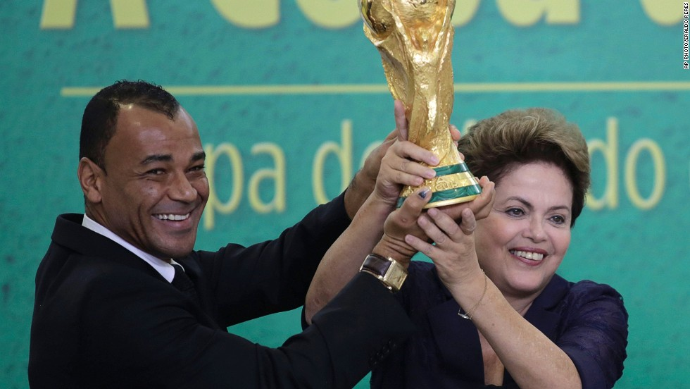 Former Brazilian soccer player, Cafu, and President Rousseff lift the trophy after it was officially presented to her.