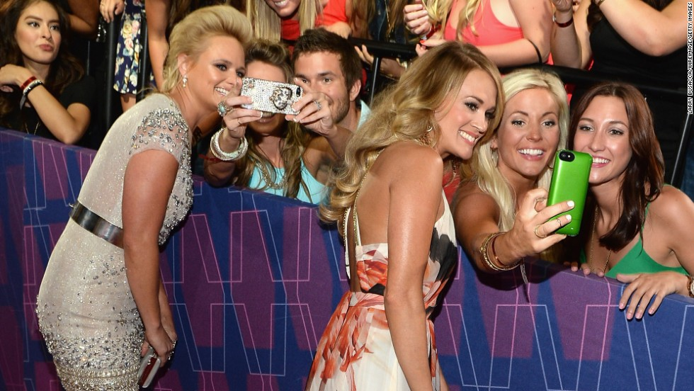 Miranda Lambert, left, and Carrie Underwood take selfies with fans on the red carpet of the 2014 CMT Music Awards on Wednesday, June 4, in Nashville.
