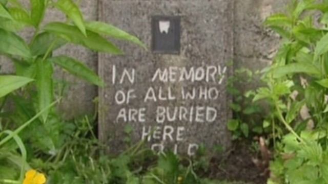 A marker to those buried at a former home for unwed mothers sits against a stone wall.