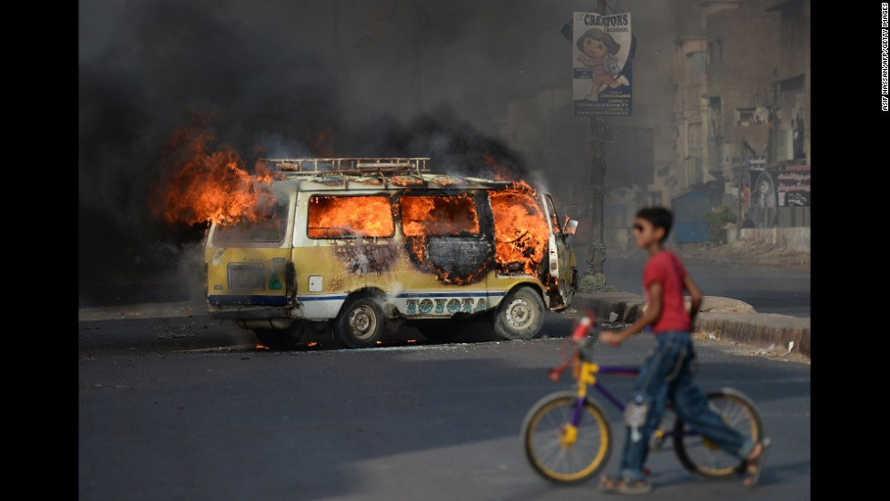 "A young boy wheels his bicycle past a burning vehicle in Karachi, Pakistan, after Altaf Hussain, leader of one of Pakistan's most powerful regional parties, <a href=""http://www.cnn.com/2014/06/03/world/europe/uk-pakistan-mqm-leader-arrest/"">was arrested in London</a> on Tuesday, June 3. Hussain, leader of Pakistan's Mutahida Qaumi Movement, was arrested in connection with a money laundering probe, officials of his party said. After news of the arrest, MQM called for protests in Karachi, which turned violent. The party condemned the violence."