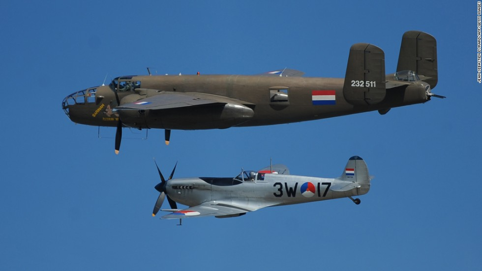 A Dutch B-25 Mitchell, top, and Spitfire fly over Arromanches-les-Bains, France, during a joint French-Dutch ceremony.