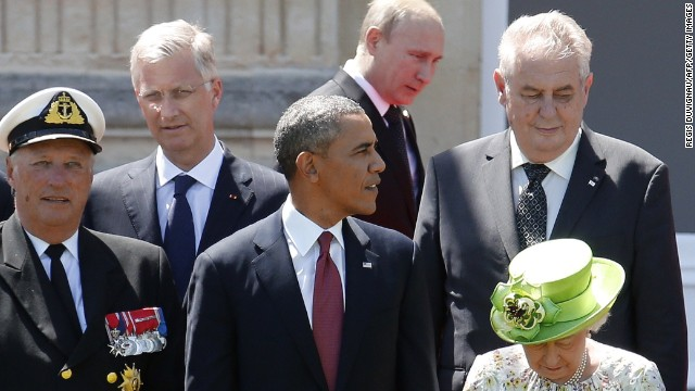 Caption:Russian President Vladimir Putin (C top) passes behind US President Barack Obama (C), Britain's Queen Elizabeth (bottom R), Norway's King Harald (L) and King Philippe of Belgium (L top) as he arrives for a group photo for the 70th anniversary of the D-Day landings at Benouville Castle, June 6, 2014. World leaders and veterans gathered by the beaches of Normandy to mark the 70th anniversary of the Allied landings in Normandy on D-Day during World War II. AFP PHOTO / POOL / Regis Duvignau (Photo credit should read REGIS DUVIGNAU/AFP/Getty Images)