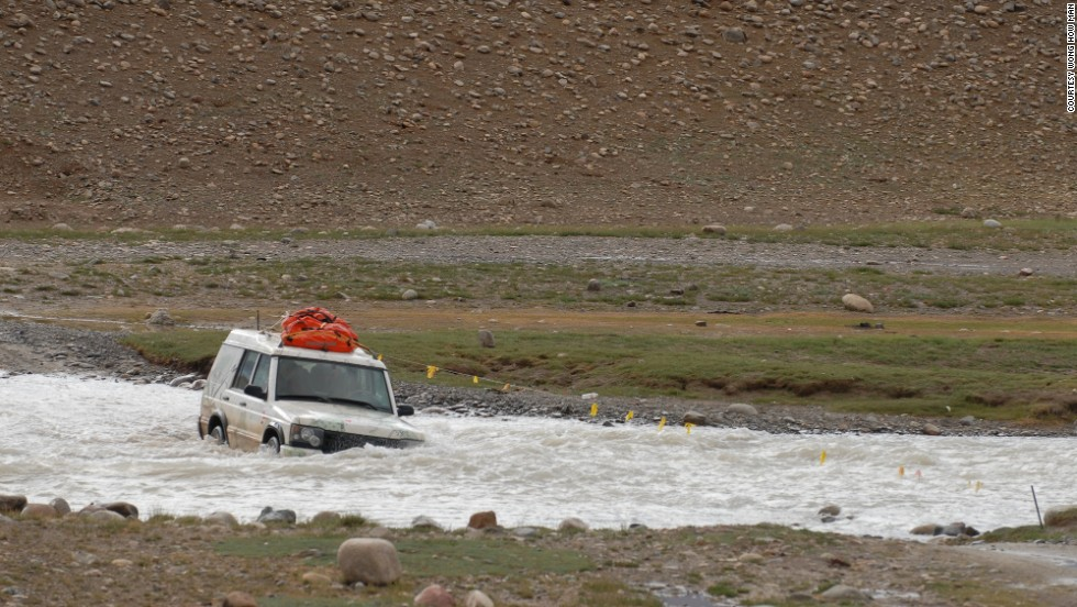 A good explorer has to have faith in his wheels. Here, Wong's expedition team crosses a river near China's border with India in a four-wheel drive vehicle.