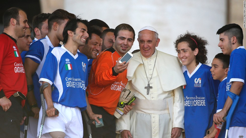 Pope Francis appears in a selfie with members of Italy's amputee soccer team Saturday, June 7, at the Vatican.