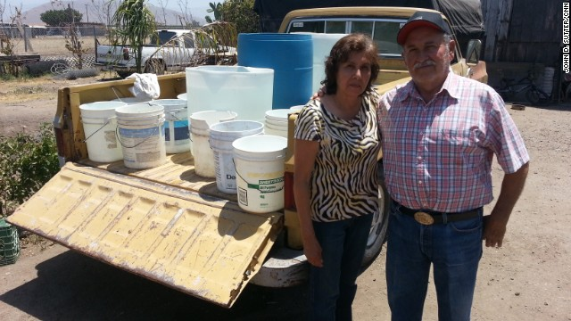 Simona and Adolfo Magana have no running water; they fill these buckets from a neighbor's tap.