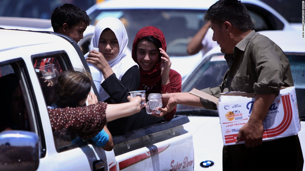 'Iraqi families are given water as they gather at a Kurdish checkpoint on June 10.' from the web at 'http://i2.cdn.turner.com/cnnnext/dam/assets/140611080717-04-iraqi-civilians-flee-mosul-horizontal-large-gallery.jpg'