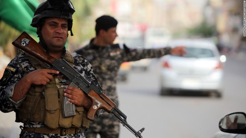 'Iraqi police stand guard at a checkpoint in Baghdad.' from the web at 'http://i2.cdn.turner.com/cnnnext/dam/assets/140611080734-07-iraqi-civilians-flee-mosul-horizontal-large-gallery.jpg'