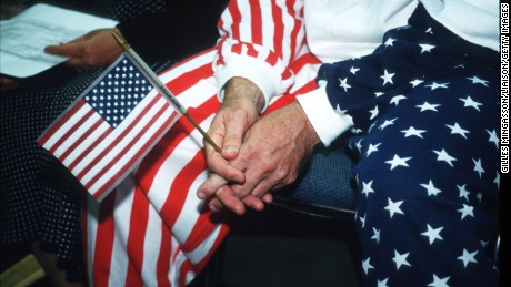 240743 25: An individual holds an American flag during the ceremony at the Convention Center September 13, 1995 in Los Angeles, CA. During the naturalization ceremonies, the US District Court administers the Oath of Allegiance to qualified applicants for US citizenship, which allows them to participate in the elections. (Photo by Gilles Mingasson/Liaison)