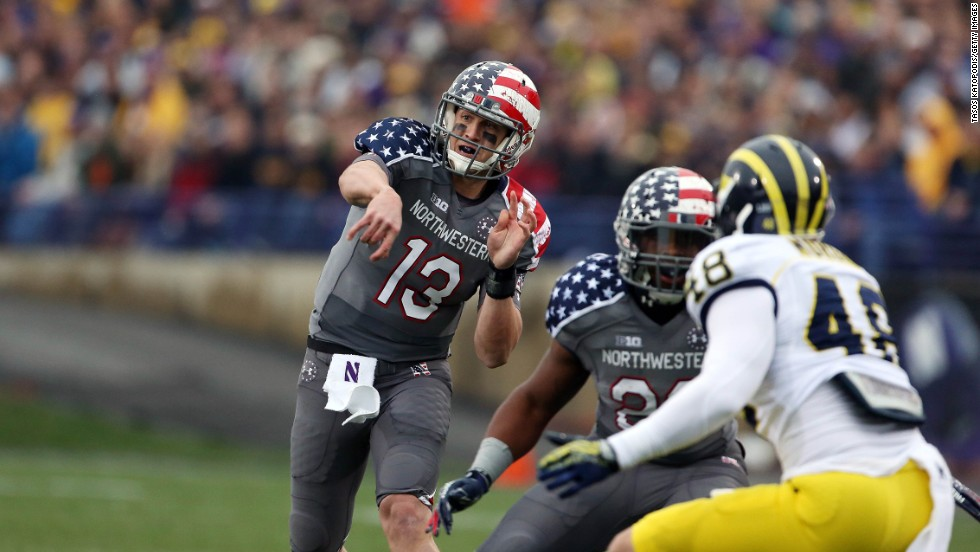 Trevor Siemian, a quarterback for the Northwestern Wildcats, tries to complete a pass against the Michigan Wolverines in 2013. The school wore the patriotic jerseys to help raise money for the Wounded Warrior Project, a nonprofit group that assists U.S. veterans.