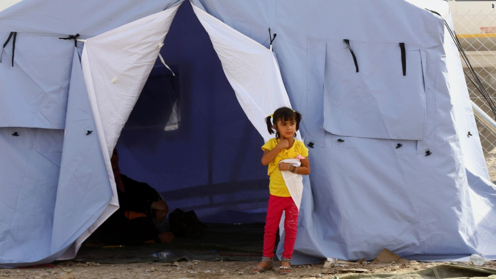 'A girl from Mosul stands outside her family's tent at a refugee camp near Erbil on Wednesday, June 11.' from the web at 'http://i2.cdn.turner.com/cnnnext/dam/assets/140612075437-iraq-mosul-flee-0611-horizontal-large-gallery.jpg'