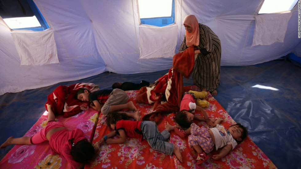 'Young refugees sleep in a tent at a temporary camp in Aski Kalak, Iraq, on June 12.' from the web at 'http://i2.cdn.turner.com/cnnnext/dam/assets/140612084649-01-iraq-mosul-0612-horizontal-large-gallery.jpg'