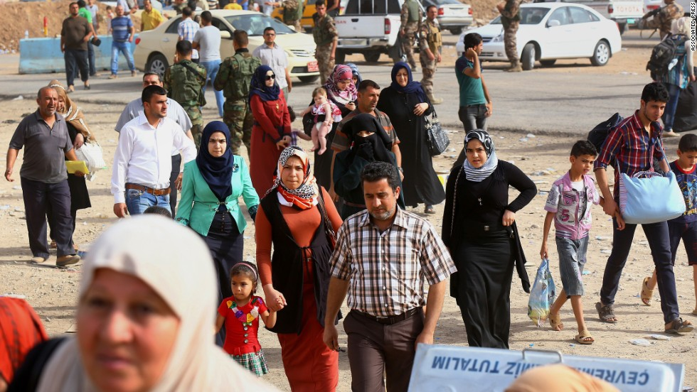 'Iraqi refugees pass an area in Erbil on June 12.' from the web at 'http://i2.cdn.turner.com/cnnnext/dam/assets/140612111905-03-iraqi-refugees-0612-horizontal-large-gallery.jpg'