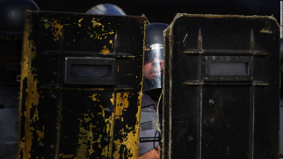 Brazilian police stand behind shields during clashes with protesters.