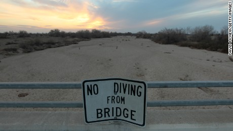 A sign from wetter times warns people not to dive from a bridge over the Kern River, which has been dried up by water diversion projects and little rain, on February 4, 2014 in Bakersfield, California. Now in its third straight year of unprecedented drought, California is experiencing its driest year on record, dating back 119 years.