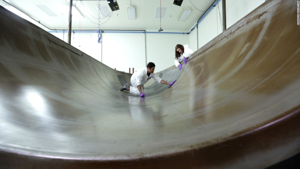 Technicians use sheets of super-strong, lightweight carbon composite materials for a process that reinforces the spaceship's fuselage.