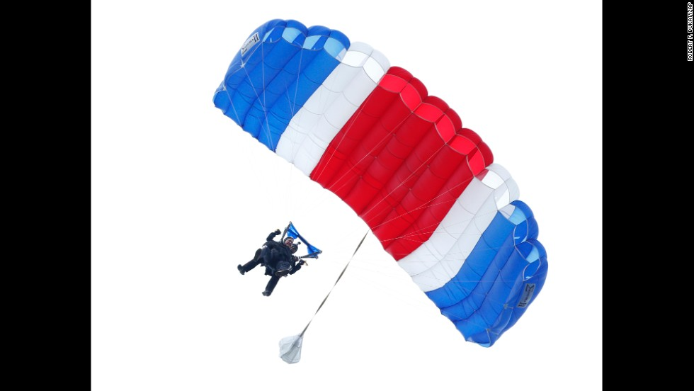 "Former U.S. President <a href=""http://www.cnn.com/2014/06/12/politics/gallery/george-h-w-bush/index.html"">George H.W. Bush</a> floats to the ground Thursday, June 12, during a tandem parachute jump near his home in Kennebunkport, Maine. Bush was strapped to Mike Elliott, a retired member of the Army's Golden Knights parachute team, as he made the jump to celebrate his 90th birthday."