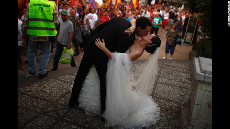 While they're photographed for their wedding at a public garden in Malaga, Spain, Veronica Munoz and Carlos Benitez are encouraged to kiss by people protesting at an anti-monarchy rally Saturday, June 7.