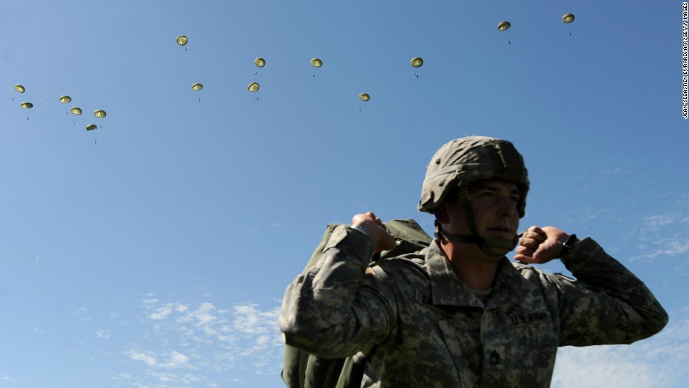 "A man watches paratroopers in the sky during a D-Day commemoration event held Sunday, June 8, in Sainte-Mere-Eglise, France. It has been 70 years since D-Day, <a href=""http://www.cnn.com/2012/06/05/world/gallery/d-day/index.html"">the largest seaborne invasion in history</a> and a major turning point in World War II."