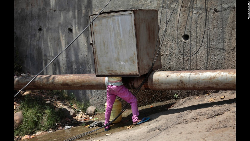 A boy collects drinking water from a leaking pipeline on the outskirts of Jammu, India, on Monday, June 9. Temperatures soared past 45 degrees Celsius (113 degrees Fahrenheit) at several locations in northern India.