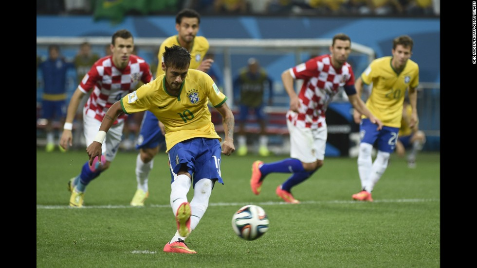 "Brazil forward Neymar strikes the ball to <a href=""http://www.cnn.com/2014/06/12/football/gallery/world-cup-goals/index.html"">score a penalty</a> and give his team a 2-1 lead in the second half against Croatia."
