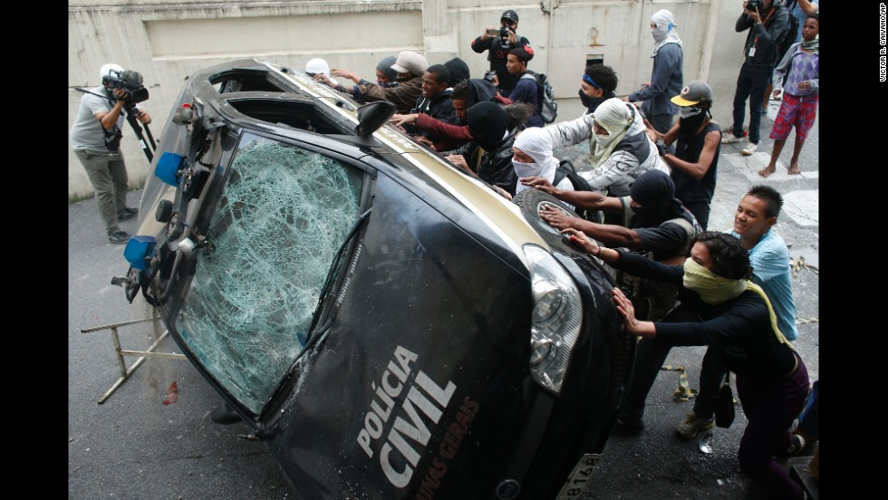 Demonstrators push over a police car during a World Cup protest in Belo Horizonte, Brazil, on Thursday, June 12.