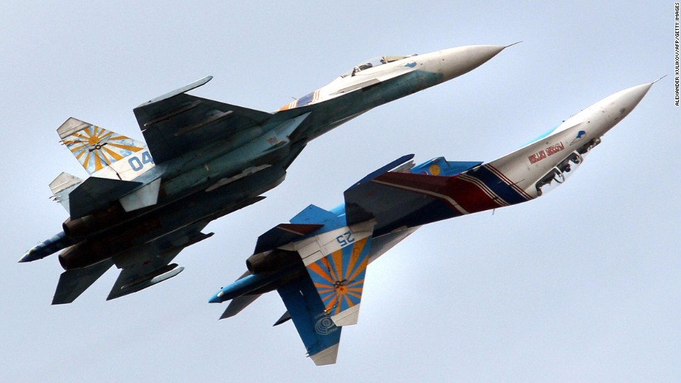 "A Russian Air Force flight demonstration team performs with their Su-27 jet fighters over St. Petersburg, Russia. An Su-27 ""showed its belly"" to a U.S. reconnaissance jet in April 2014."