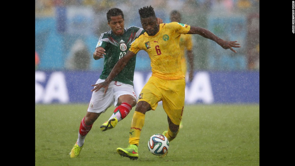 Song controls the ball as Mexico's Giovani dos Santos, left, challenges him.