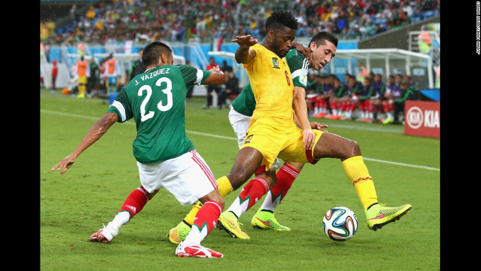 Alex Song of Cameroon is challenged by Mexico's Jose Juan Vazquez, left, and Herrera during the first half.