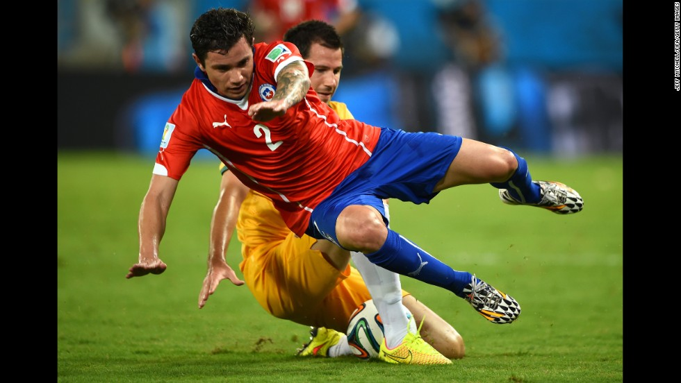 Eugenio Mena of Chile is brought down during the game.